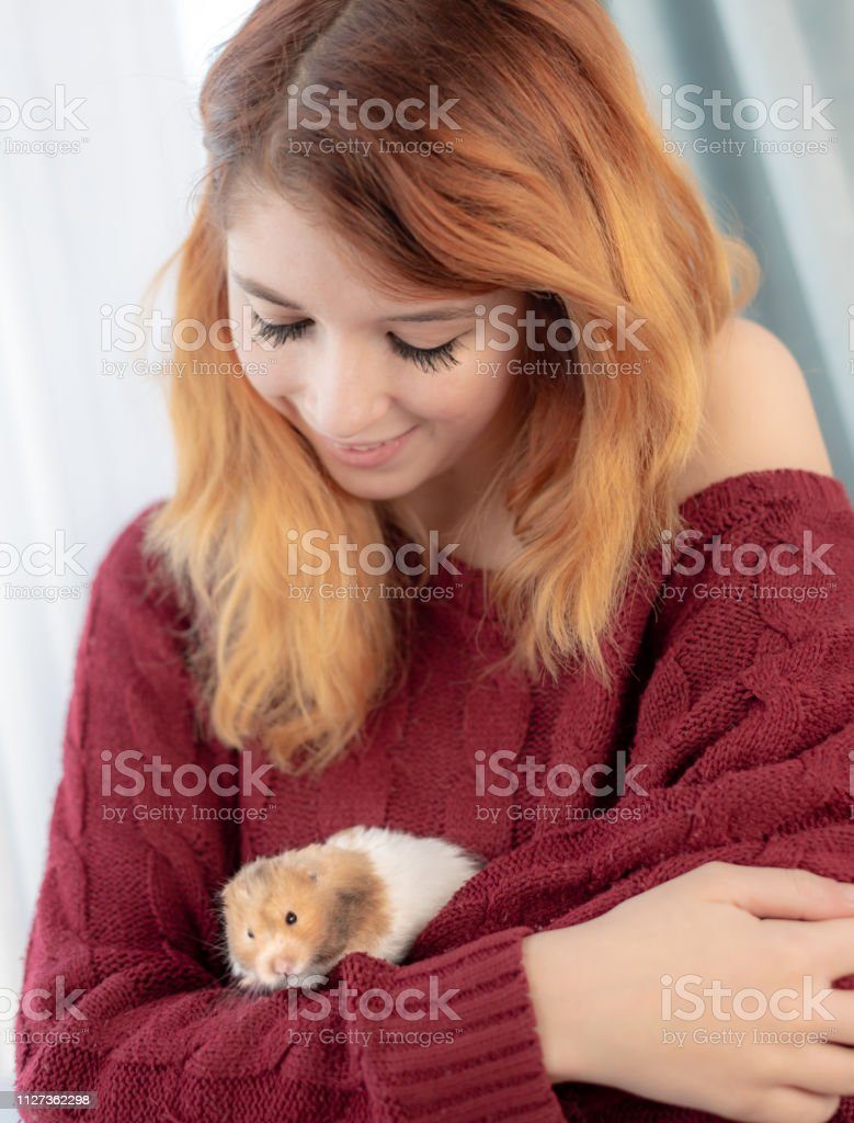 Girl cuddles her pet hamster stock photo