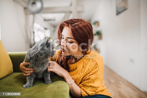 537697440istockphoto Girl cuddling cat 1128000666