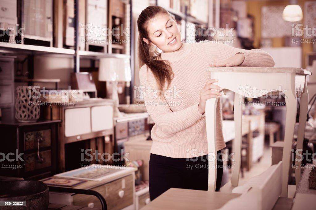 Girl customer choosing bedside in the furniture store indoors