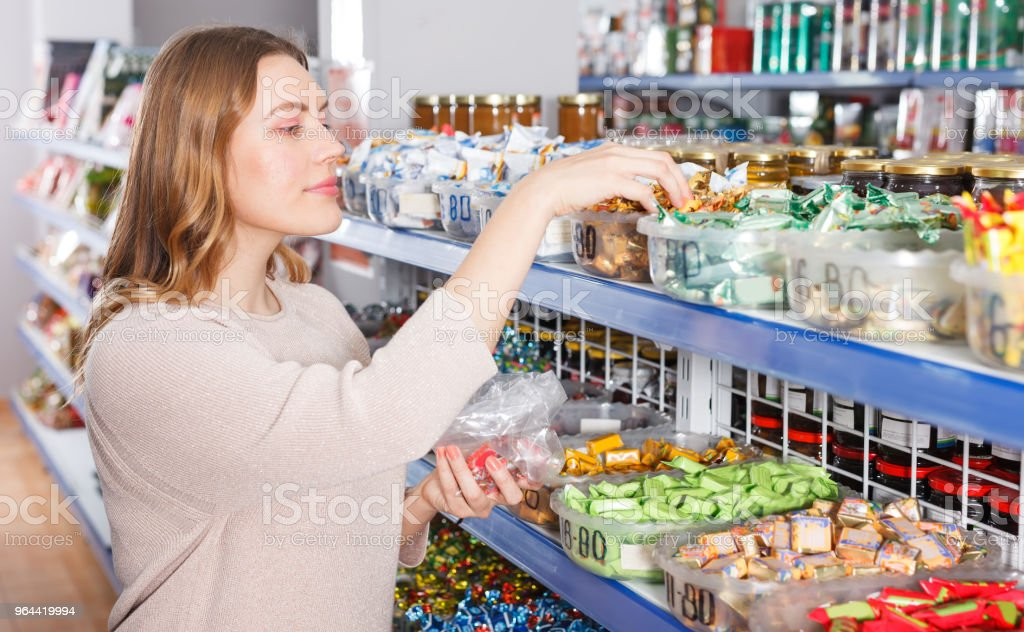 girl customer choosing  variety candies - Royalty-free Adult Stock Photo