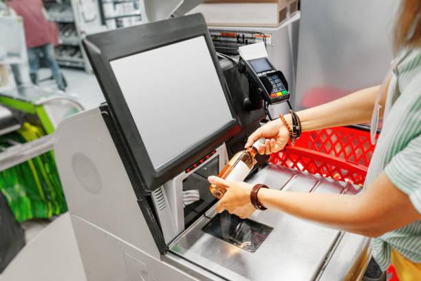 Mädchen Kunde scannt Flasche Wein an der Selbstbedienungskasse im Lebensmittel-Supermarkt-Shop – Foto