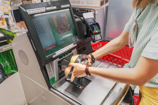 Girl customer scans products at the self-service checkout in the grocery shop stock photo