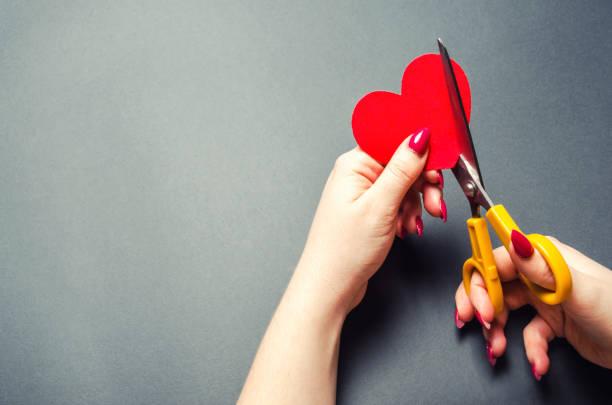 女の子は、ハサミで赤いハートをカットします。関係、喧嘩、離婚分割の概念。みんなの裏切り。あなたの愛する人のための気持ちの損失 - 別れ ストックフォトと画像