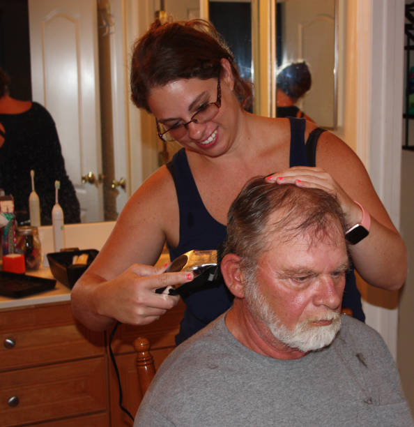 Girl cutting older man's hair stock photo