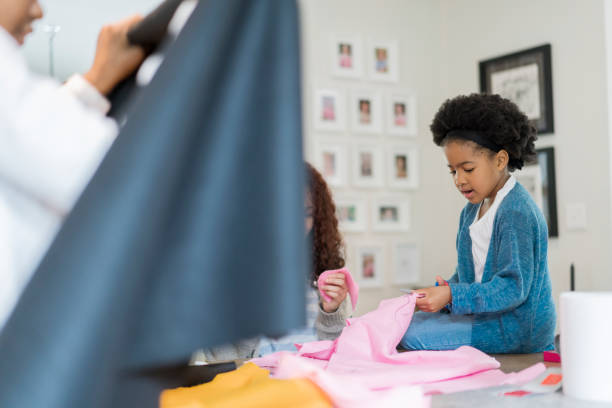 Girl cutting pink fabric with family at home stock photo
