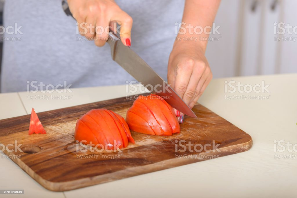 Girl cutting tomatoes with a knife stock photo