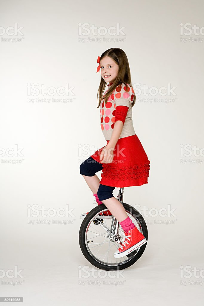 A girl cycling on a unicycle stock photo