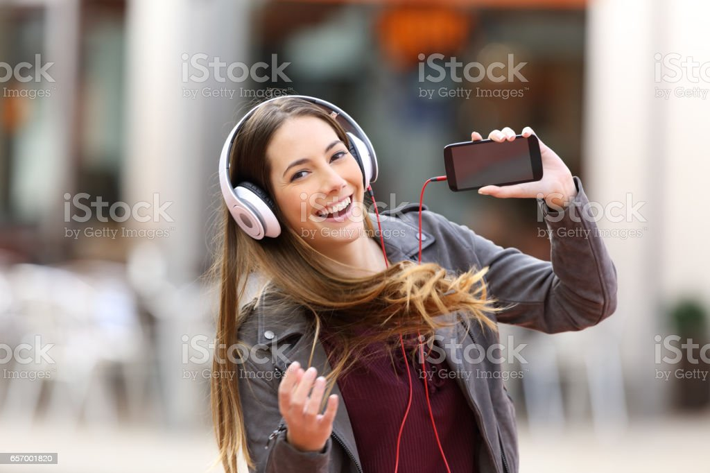 girl dancing and listening music looking at you stock