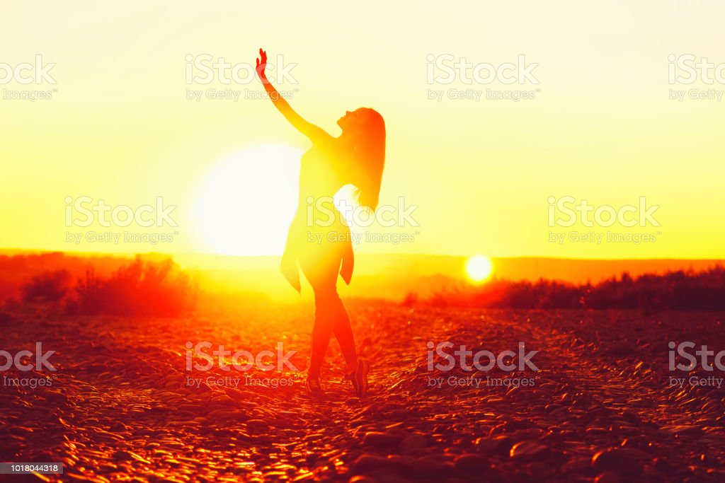 girl dancing at sunset on the beach stock photo