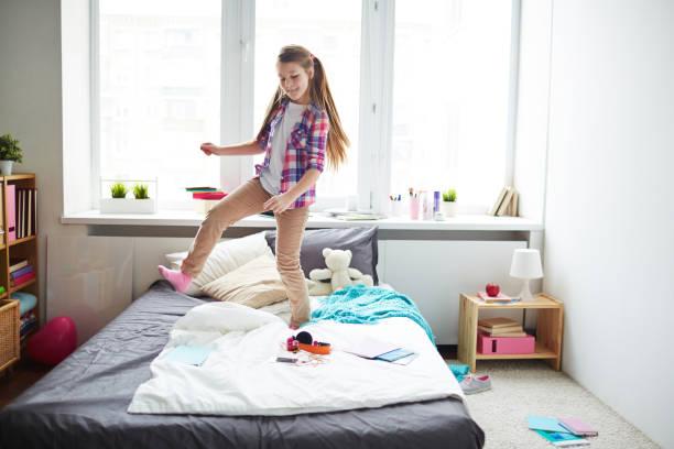 girl dancing on bed - schlafzimmer teenager stock-fotos und bilder