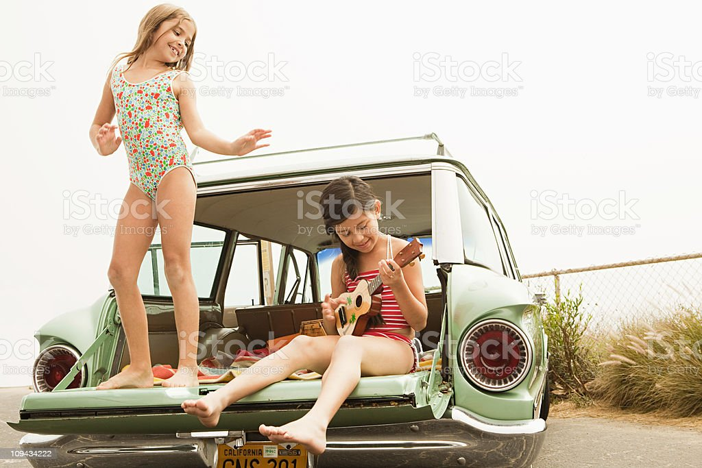 Girl dancing on car boot, another girl playing guitar stock photo
