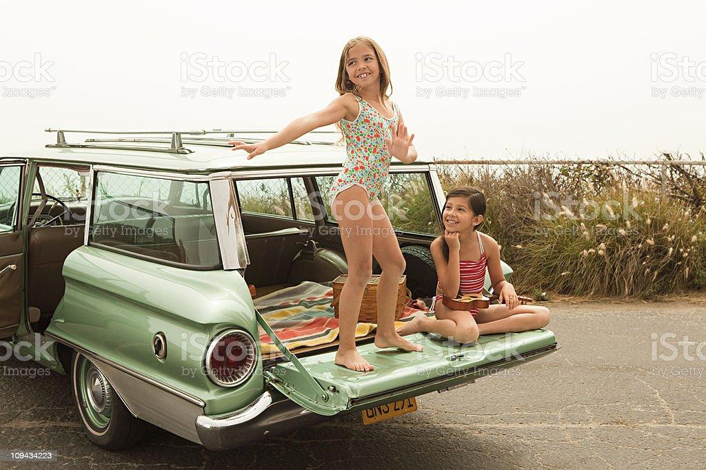 Girl dancing on car boot stock photo