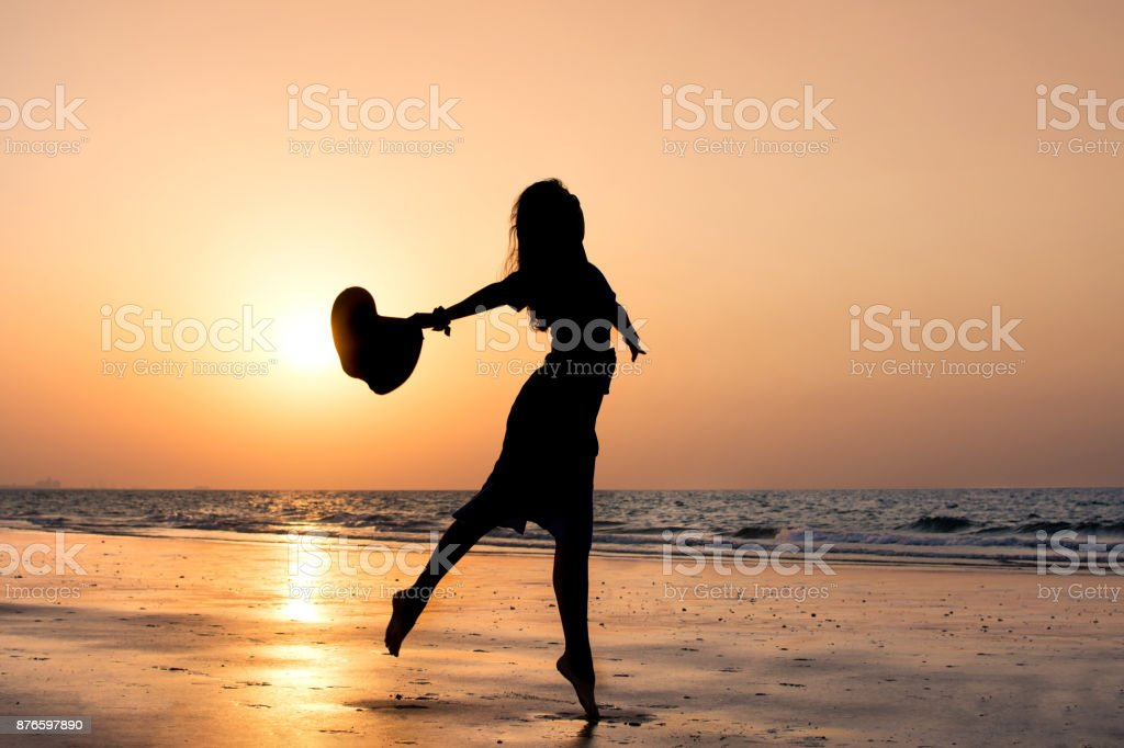 Girl dancing on the beach at sunset stock photo
