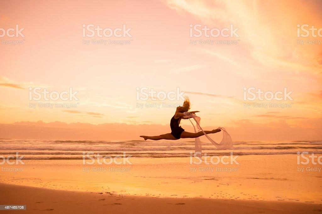 Girl dancing on the beach stock photo