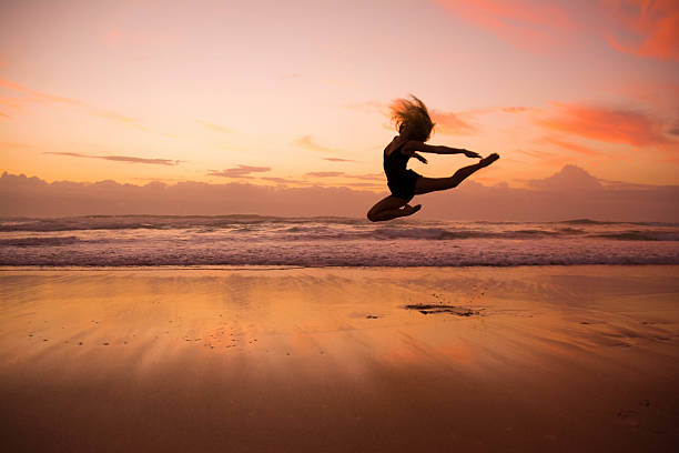 Girl dancing through the sky stock photo