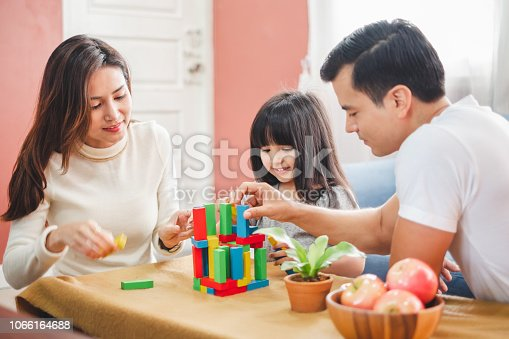 954356678 istock photo Girl daughter playing blocks toy over father and mother, happy family concept 1066164688