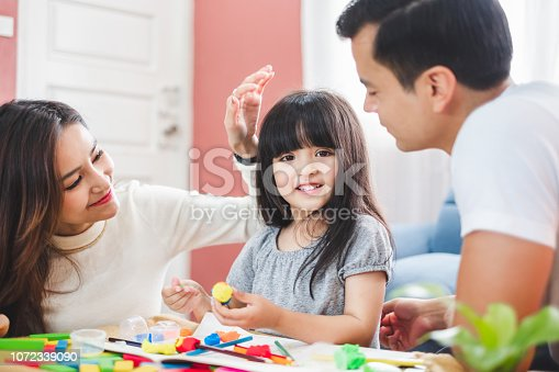 954356678 istock photo Girl daughter playing blocks toy over father and mother, happy family concept 1072339090