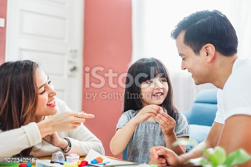 954356678 istock photo Girl daughter playing blocks toy over father and mother, happy family concept 1072340216