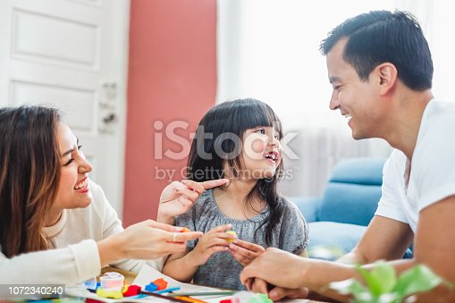 954356678 istock photo Girl daughter playing blocks toy over father and mother, happy family concept 1072340240