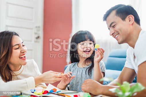 954356678 istock photo Girl daughter playing blocks toy over father and mother, happy family concept 1072340288