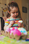 A girl decorates Easter eggs with acrylic paints & markers.