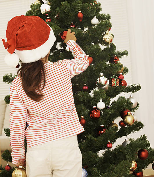 Girl decorating Christmas tree at home Rear view of a Girl decorating Christmas tree at home little girls in panties stock pictures, royalty-free photos & images
