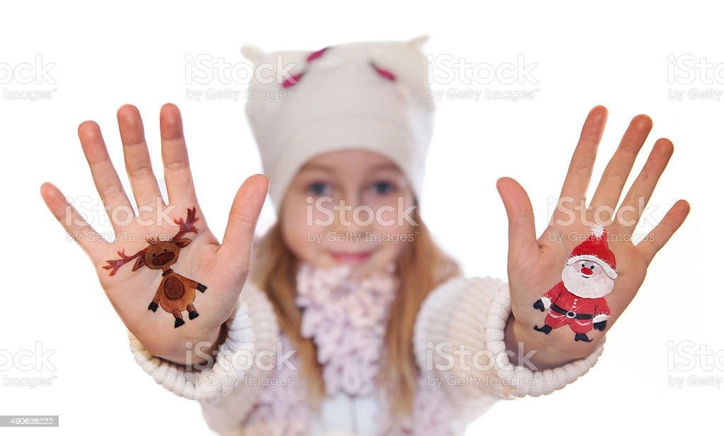 Girl demonstrating painted Christmas symbols on her hands stock photo