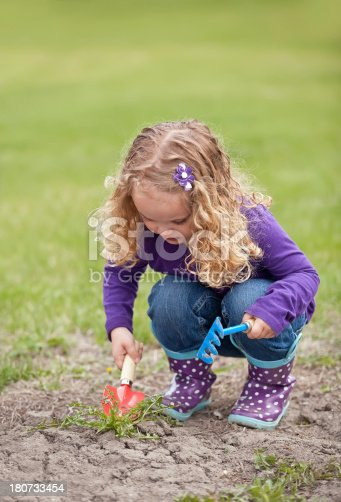 Young girl digging up weeds in an unplanted garden.