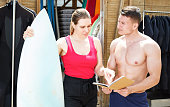 Sports female planning to rent surf outfit in beach club, discussing terms with young athletic man. Focus on woman