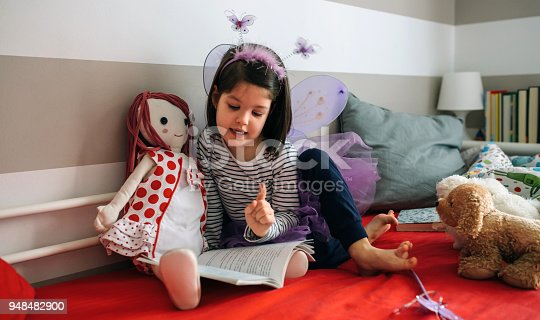 istock Girl disguised reading a book to her doll 948482900