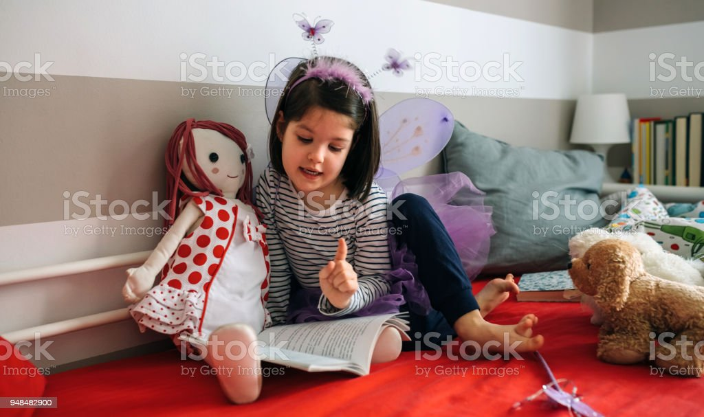 Girl disguised reading a book to her doll stock photo