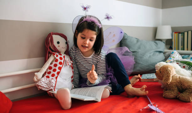 Girl disguised reading a book to her doll Little girl disguised as a butterfly sitting on the bed reading a book to her rag doll dressing up stock pictures, royalty-free photos & images