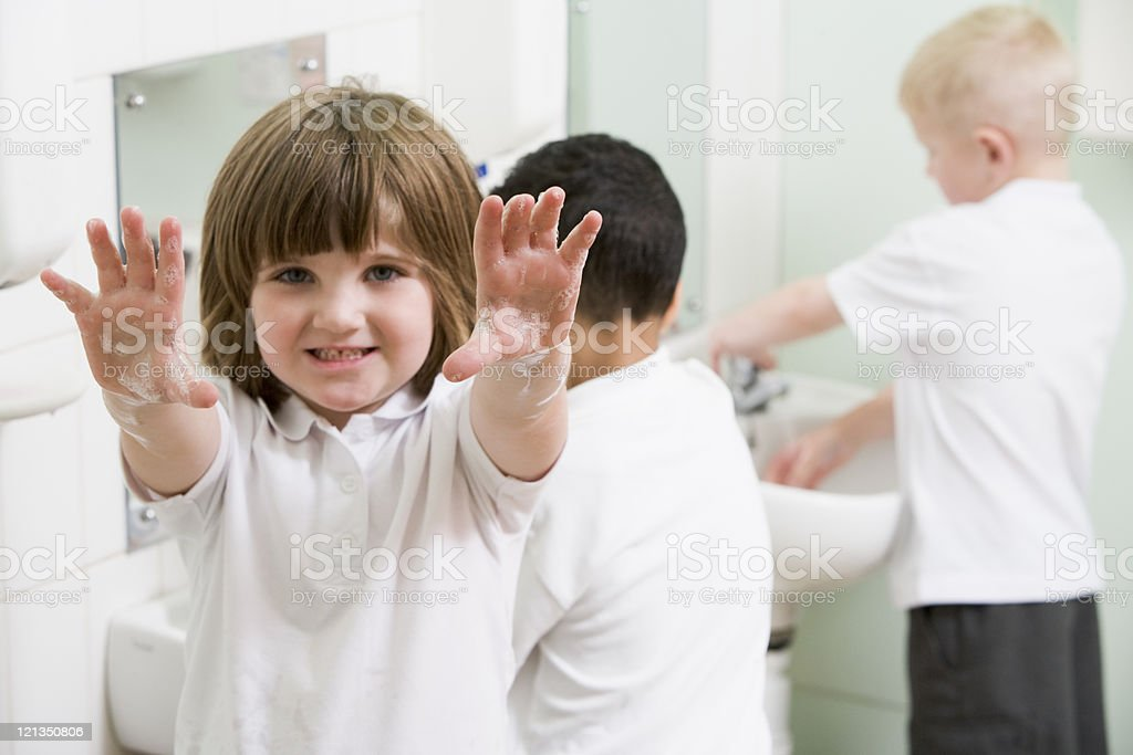 Girl displaying her soapy hands in a primary school bathroom stock photo