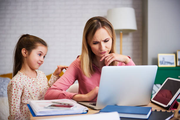 Girl disturbing her mother to work at home Girl disturbing her mother to work at home inconvenience stock pictures, royalty-free photos & images