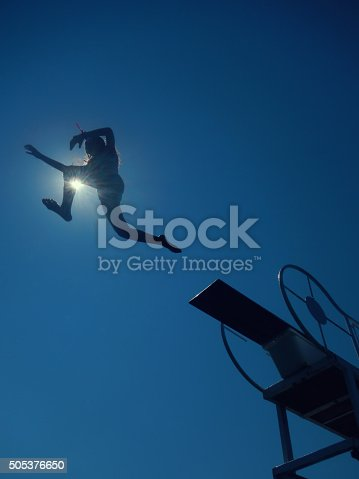girl jumping to sea from diving board
