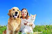 Young girl is holding a cat in her arms, a dog is next to her and they are relaxing.