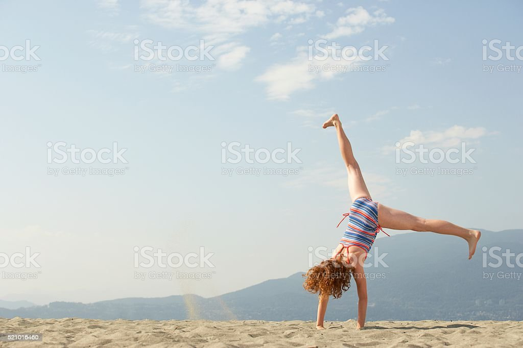 Girl doing a cartwheel on the beach stock photo