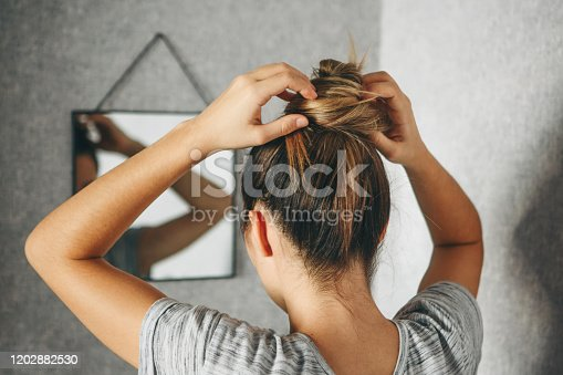 Girl does hairstyle or hair style in front of a mirror in the room