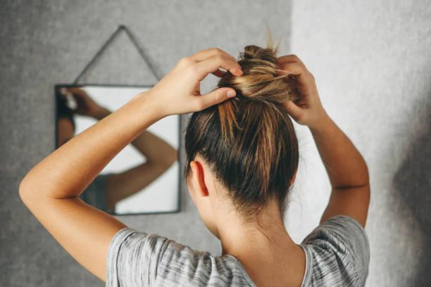 Mädchen tun Frisur am Spiegel – Foto