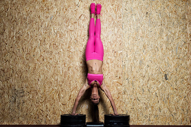 Girl doing handstand at the gym stock photo