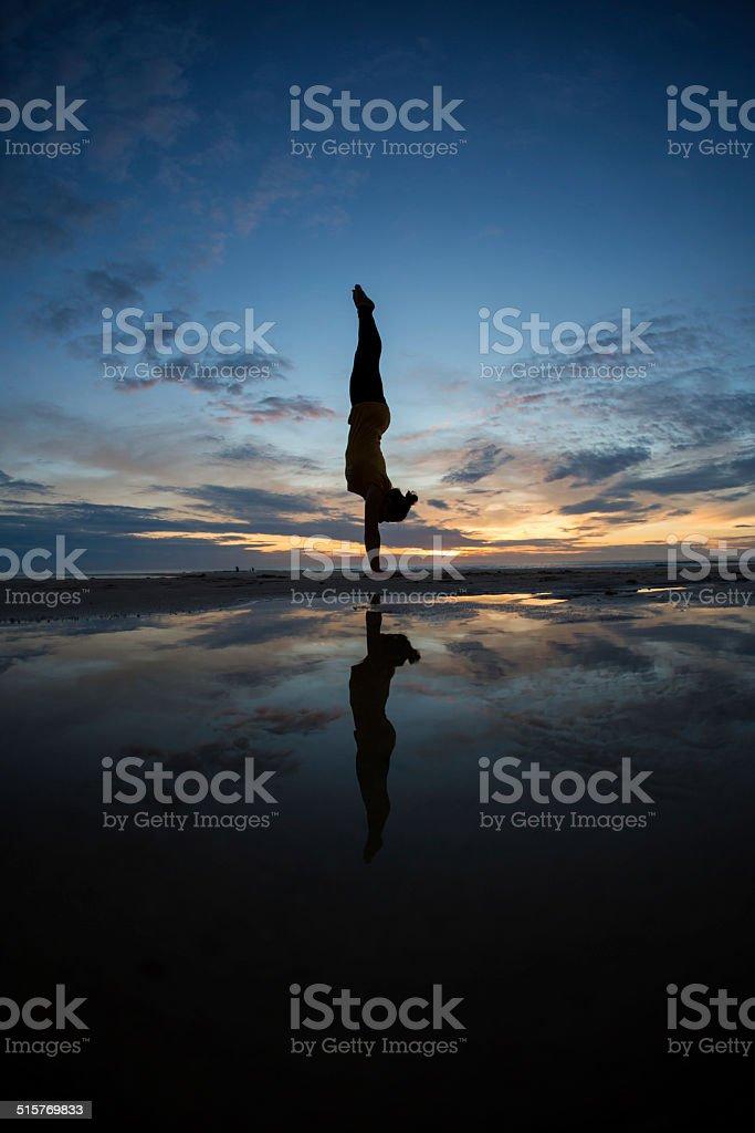 girl doing handstand on beach in sunset stock photo