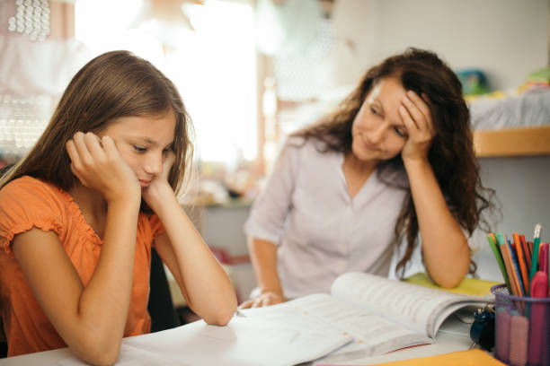 Girl doing homework with her mother at home stock photo