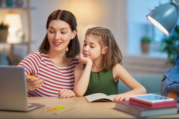 Girl doing homework with mother stock photo