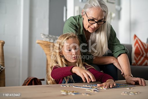 istock Girl doing jigsaw puzzle with grandmother 1161412447