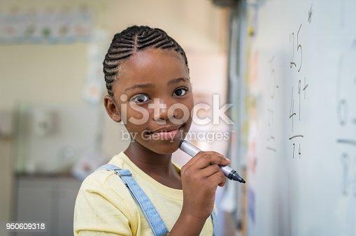 istock Girl doing math at whiteboard 950609318