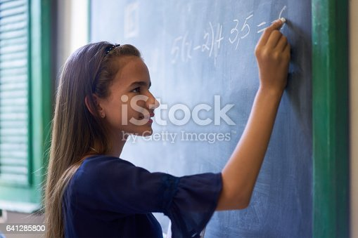istock Girl Doing Math Exercise At Blackboard In High School Class 641285800