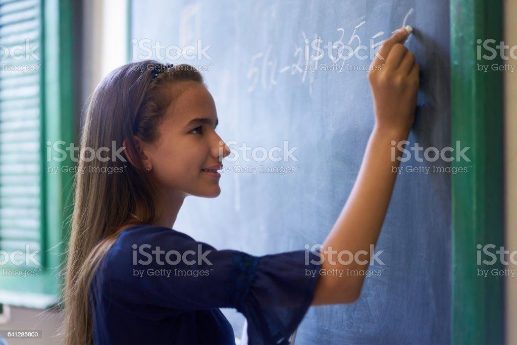 女の子が高校の授業で黒板に数学演習 ストックフォト