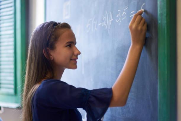 女の子が高校の授業で黒板に数学演習 - 数学の授業 ストックフォトと画像