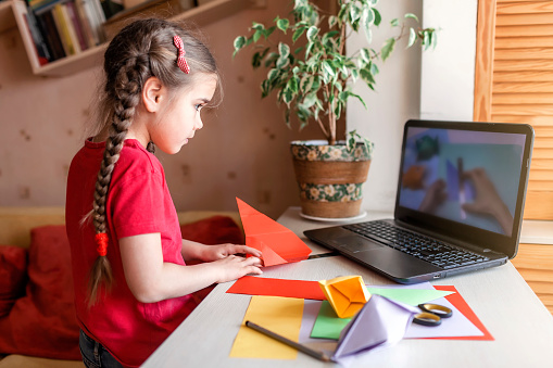 Girl doing origami fish with color paper looking video on laptop, online workshop and distant education