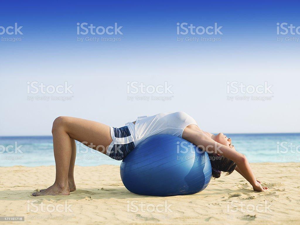 Girl doing pilates on the beach royalty-free stock photo